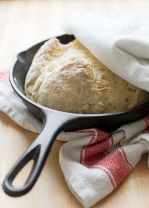 Skillet Soda Bread in a cast iron skillet with a red and ivory patterned kitchen towel alongside.