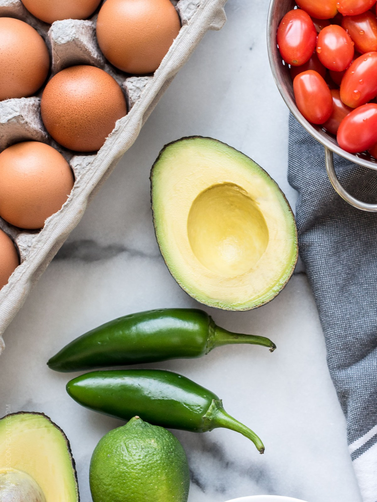 Jalapeno peppers, avocado, cherry tomatoes, and a carton of eggs.