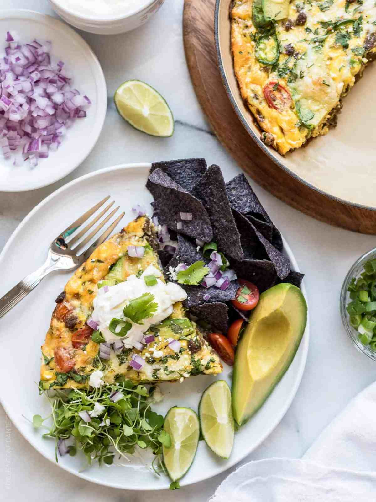 Wedge of taco frittata served with lime wedges, tortilla chips, and avocado.
