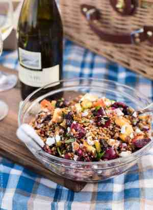 A bowl of Summer Wheat Berry Salad on a blue checkered cloth with a bottle of J. Lohr Chardonnay in the background.