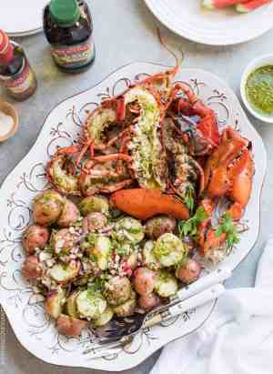 Grilled Chimichurri Lobster and Chimichurri Potato Salad is the easiest feast to come off the grill! A simple chimichurri made with good olive oil and red wine vinegar adds zing to grilled lobster and an herbed potato salad. Try it for your next barbecue!