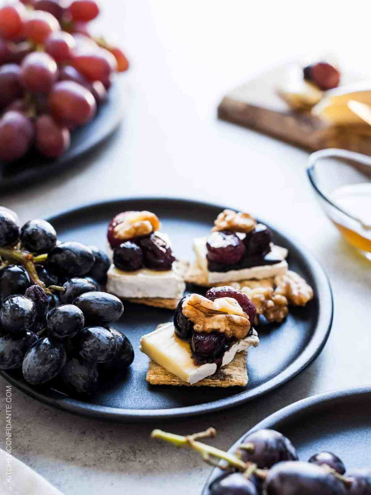 Close up view of Caramelized Grape, Brie and Walnut Bites made with TRISCUIT crackers and served on a plate.