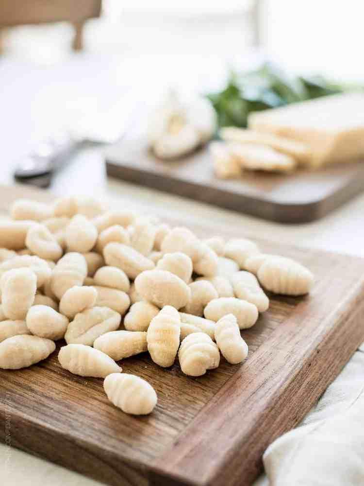 Fresh gnocchi on a wooden cutting board.