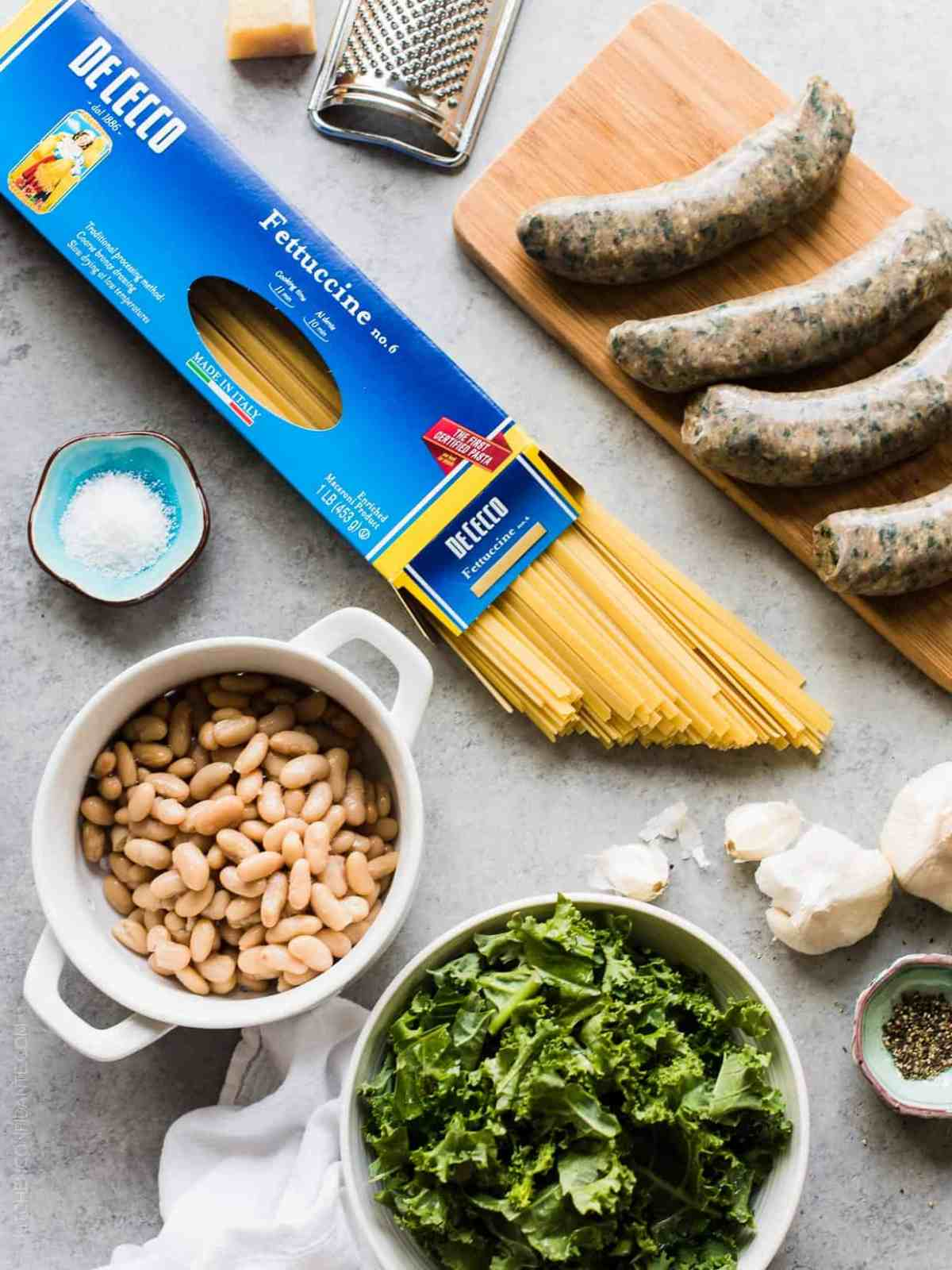 Ingredients assembled to prepare Fettuccine with Chicken Sausage, Kale and Cannellini Beans.