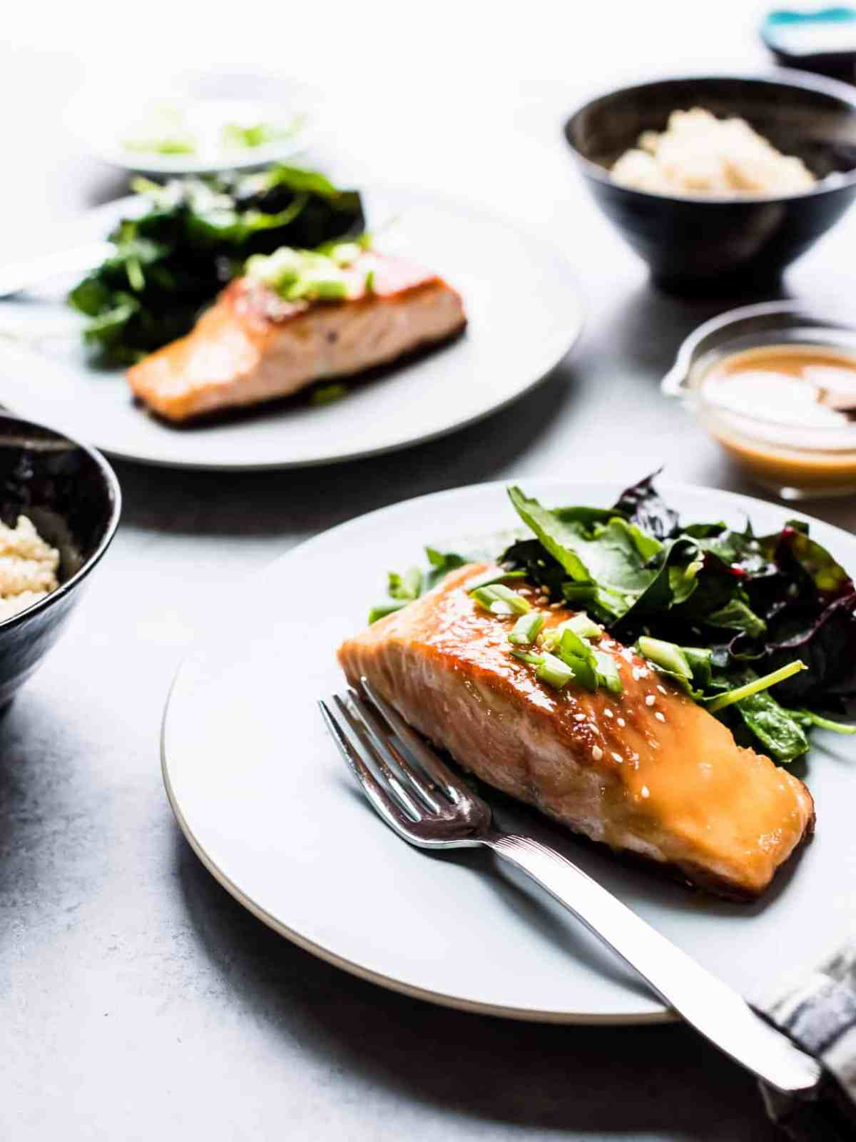 Miso Maple Glazed Salmon on a white plate served with a salad of wilted greens.