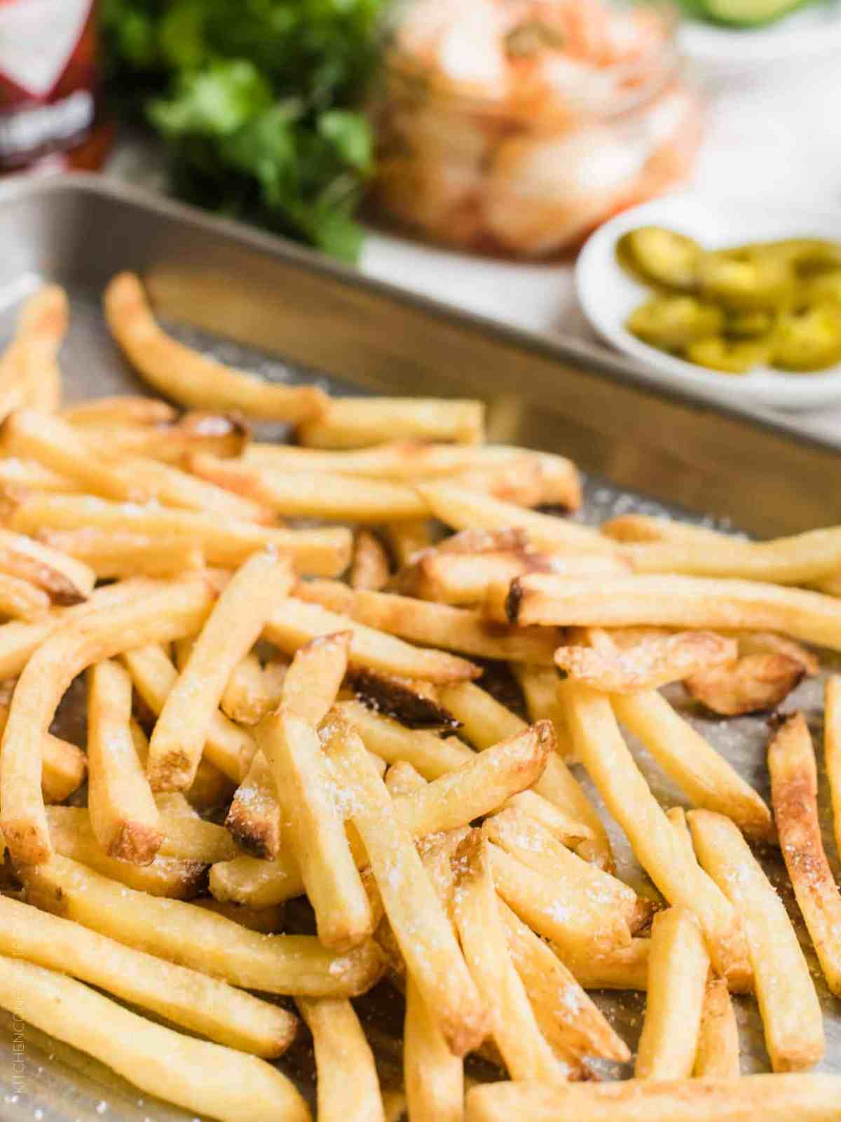 Close up view of French fries sprinkled with salt on a baking tray.