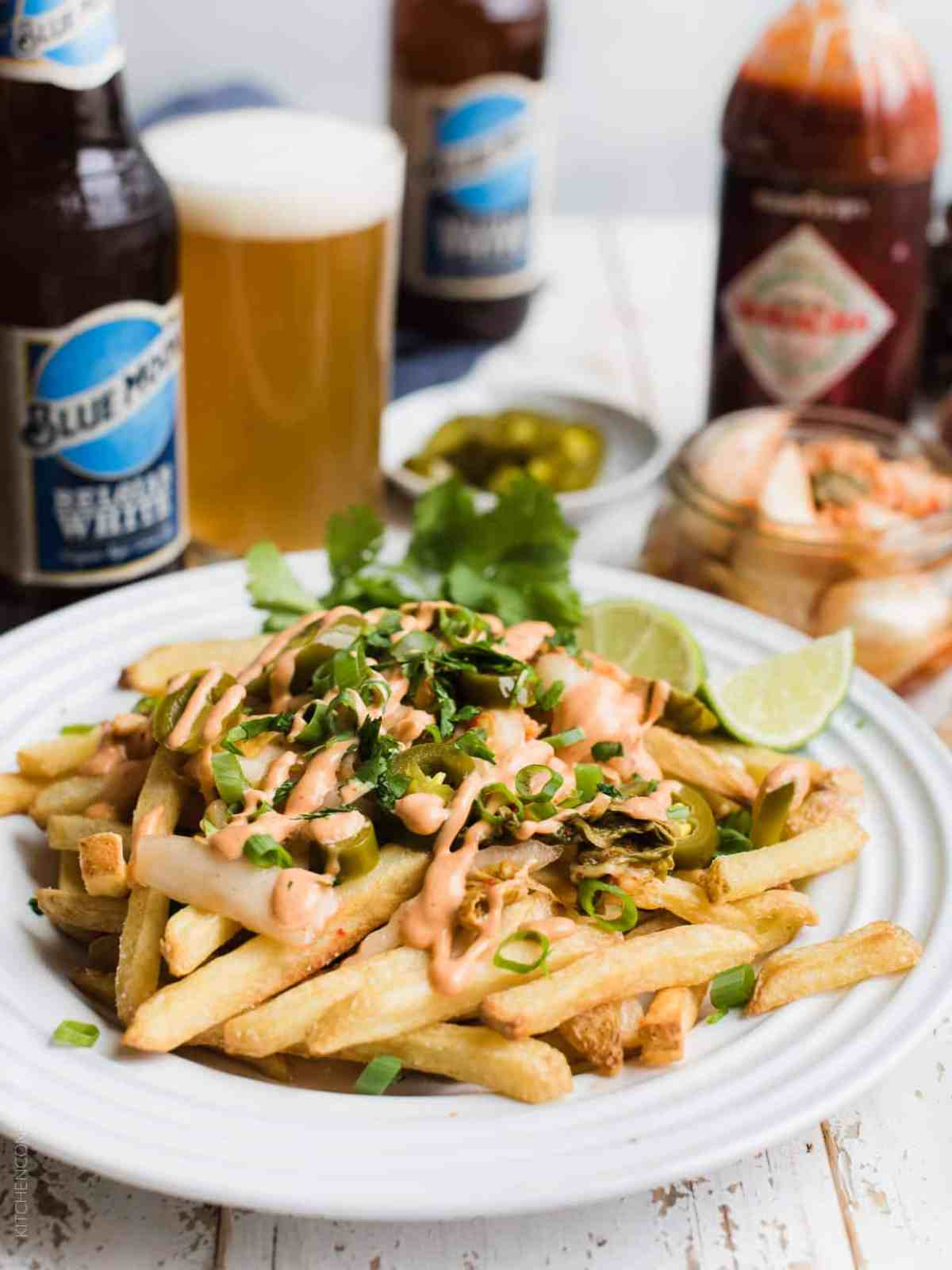 White plate filled with Kimchi French Fries with Belgian beer and a jar of kimchi in the background.