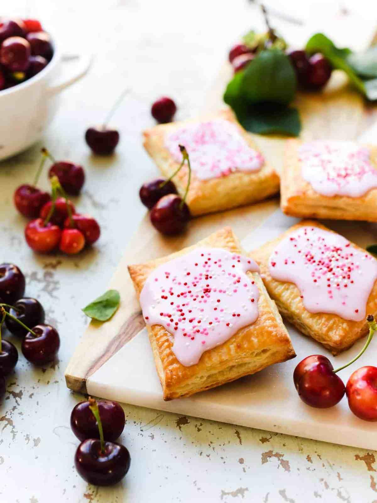 Homemade Cherry Pop Tarts surrounded by fresh cherries