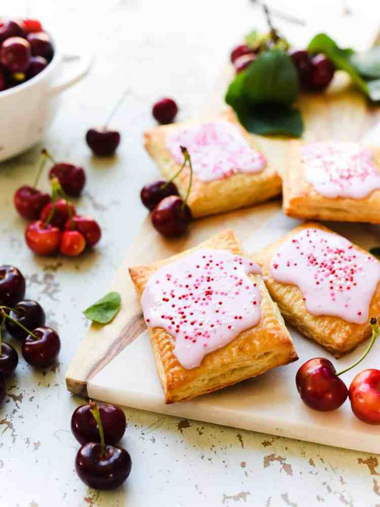 Homemade Cherry Pop Tarts with icing and sprinkles on a wood and marble serving board with fresh cherries.
