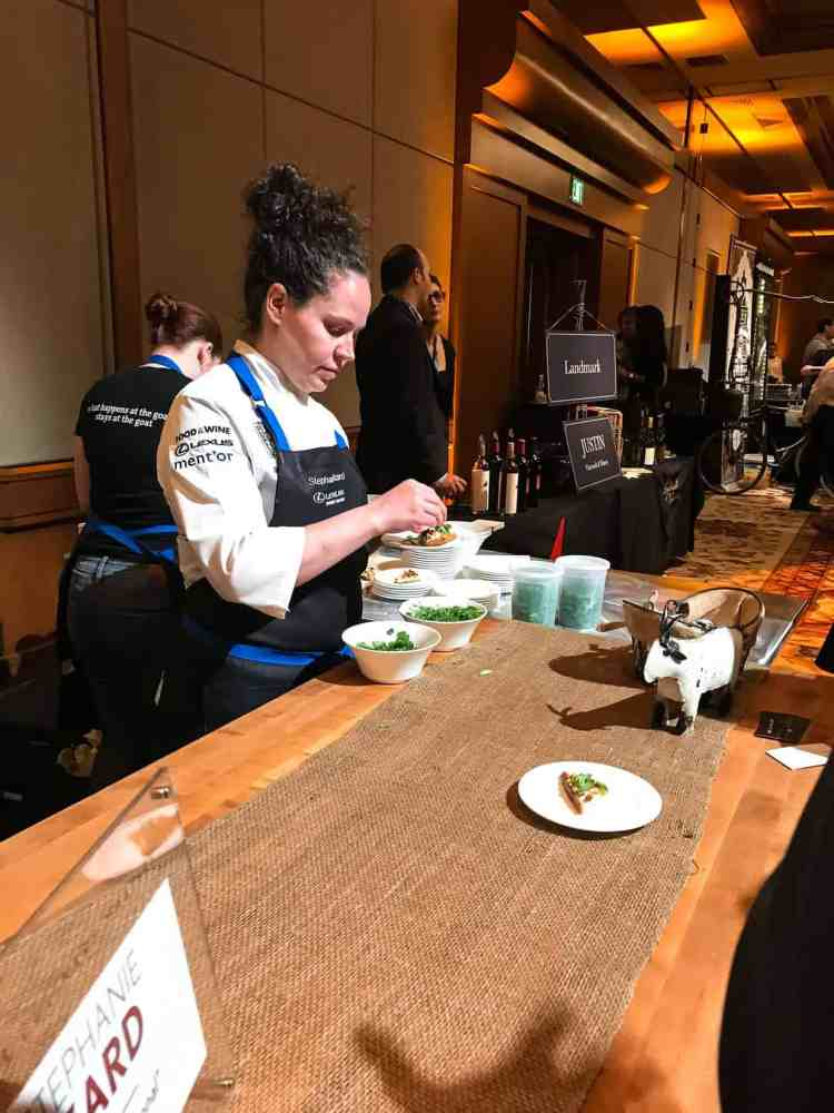 A woman in a chef coat and apron handling greens at the Pebble Beach Food & Wine.