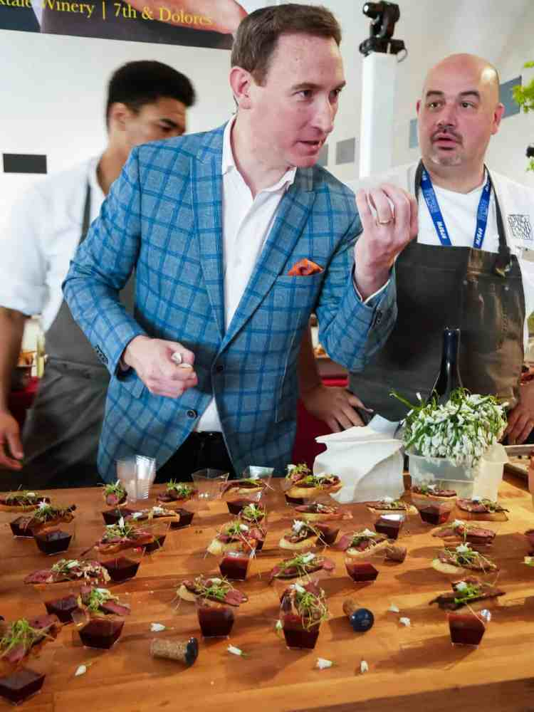Three men standing behind a wooden table of appetizers at the Pebble Beach Food & Wine.