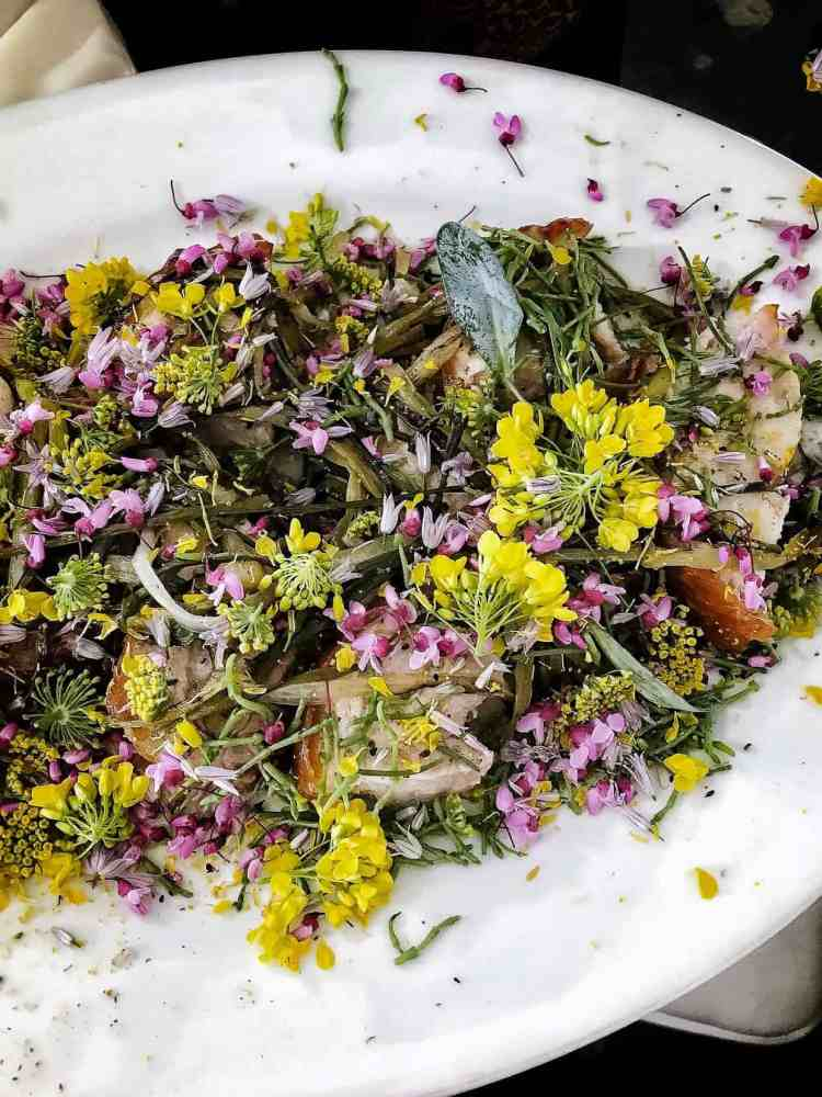 Salad with greens and yellow and purple flowers on a white plate at the Pebble Beach Food & Wine.