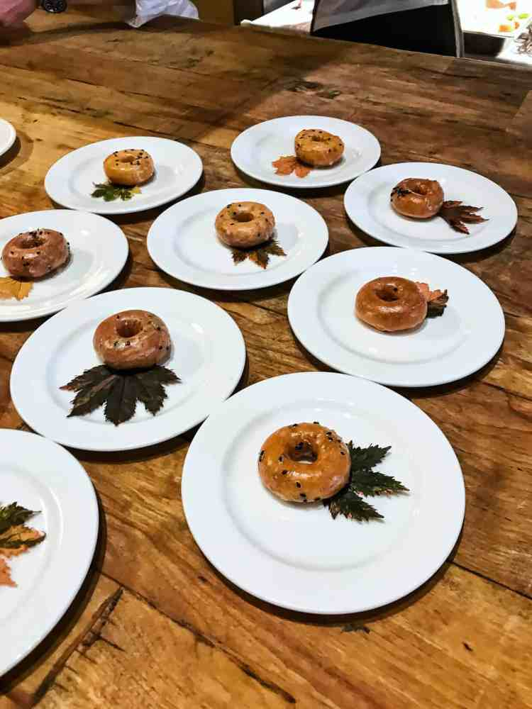 Sriracha 'Cha Mochi Donuts on white plates with green leafy garnish on a wooden table at the Pebble Beach Food & Wine.