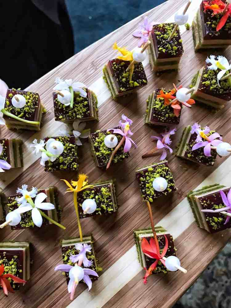 Stacks of napoleons made from savory ingredients, decorated with flowers and served on a wooden board at the Pebble Beach Food & Wine.