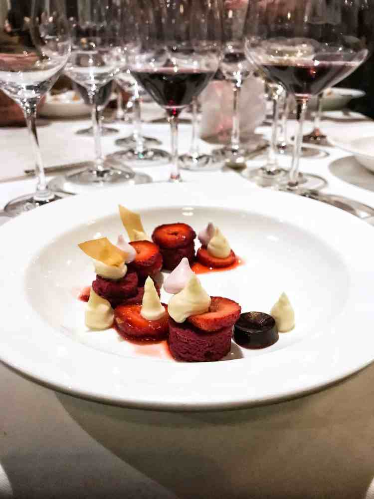 Strawberries, red velvet cake, and frosting on a white plate with wine glasses in the background at the Pebble Beach Food & Wine.