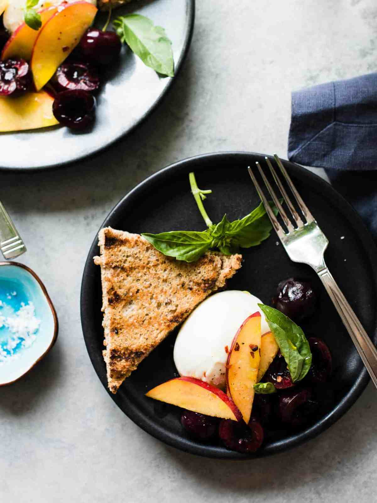Peaches, cherries, burrata, and basil on a dark plate with grilled bread.