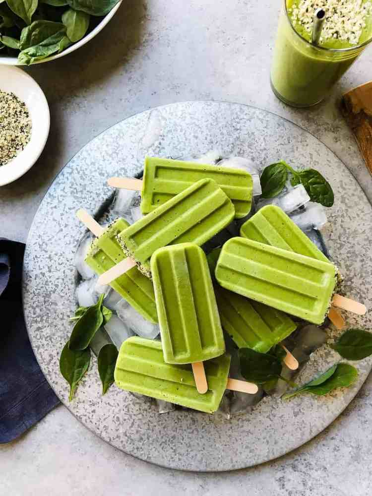 Green Smoothie Popsicles on a platter with ice cubes and fresh baby spinach leaves for garnish.
