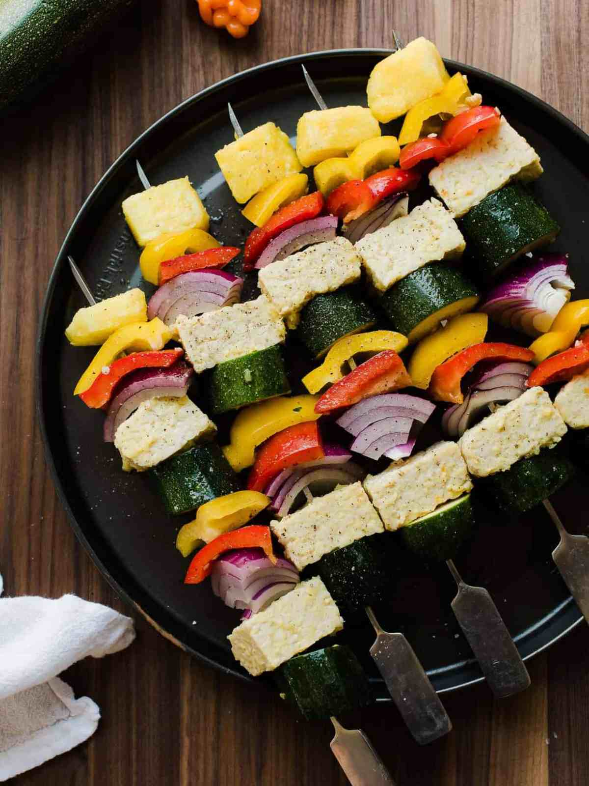 Grilled vegetable skewers with pineapple on a black plate.
