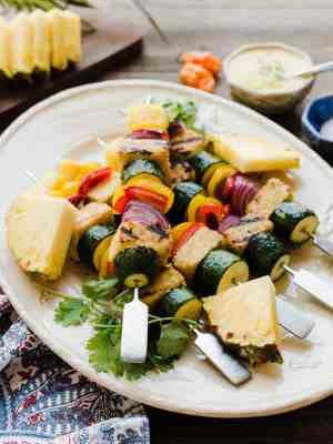 Grilled vegetable skewers with pineapple on a white plate.