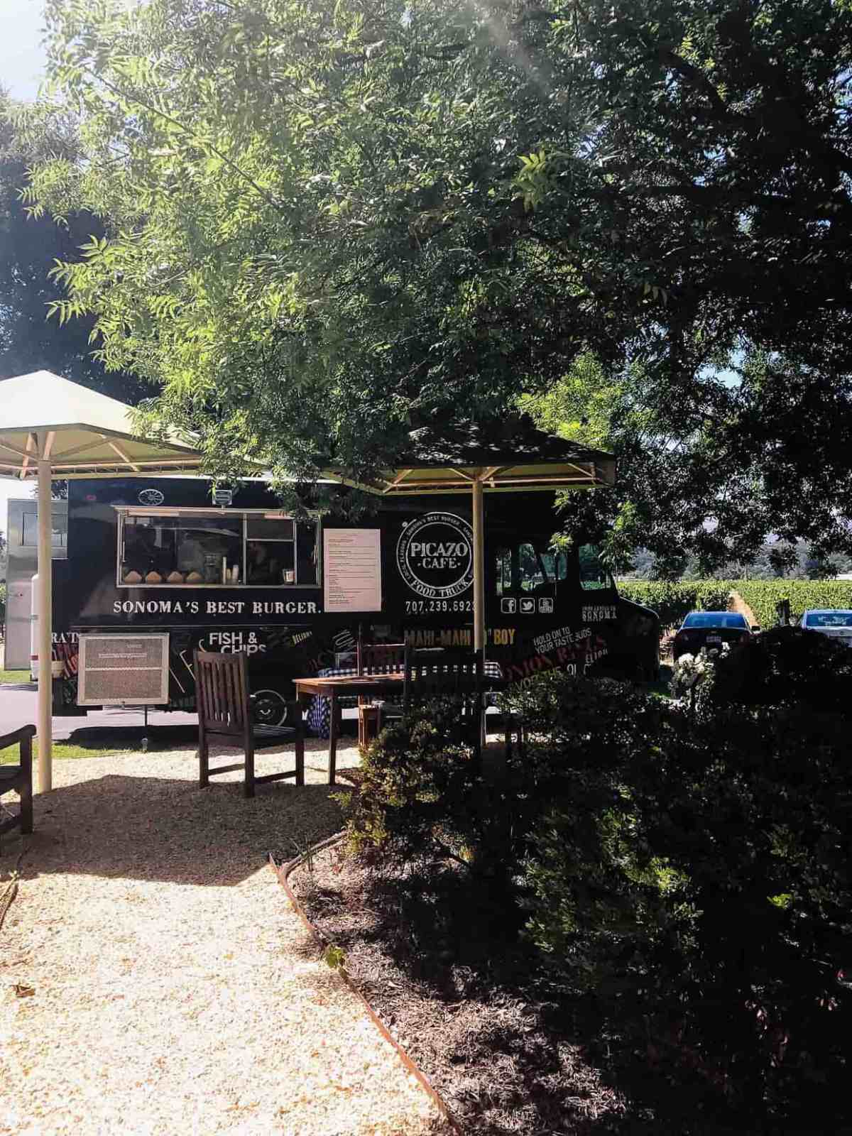 A black and white food truck parked under the shade of trees with outdoor seating.