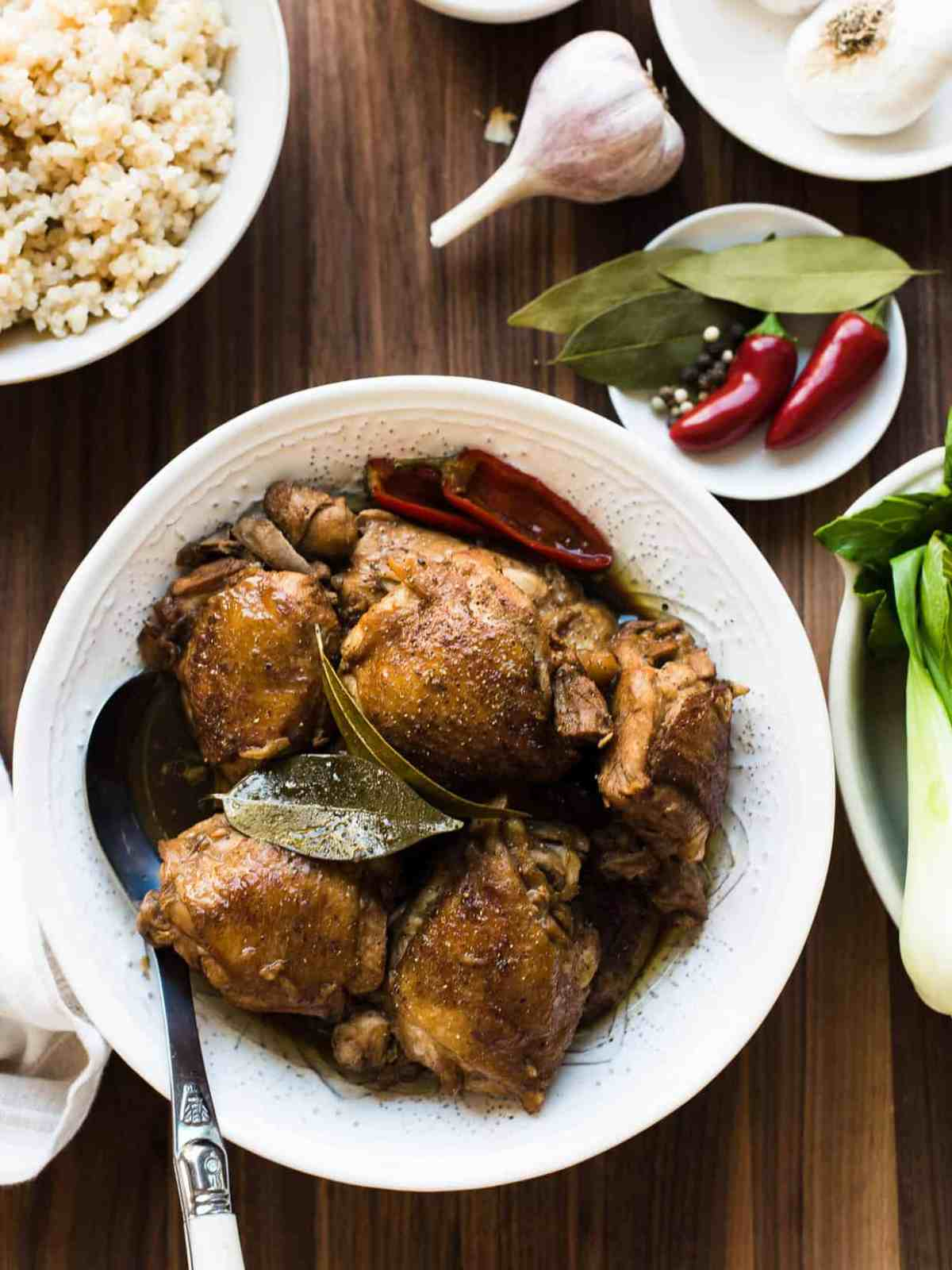 Dish of Authentic Filipino Chicken Adobo served over rice and surrounded by garlic.