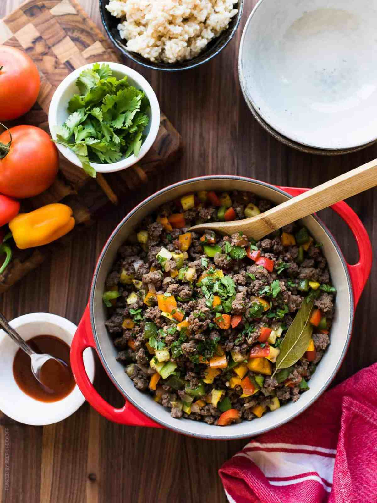 Red dutch oven of Filipino-style Picadillo surrounded by fresh ingredients and brown rice.