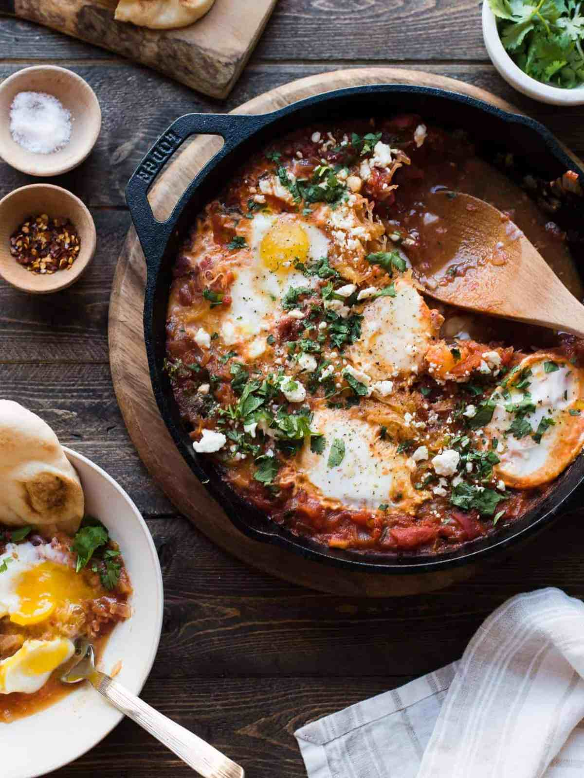 Cast iron pan filled with Spaghetti Squash Shakshuka and surrounded with garnishes and seasonings.