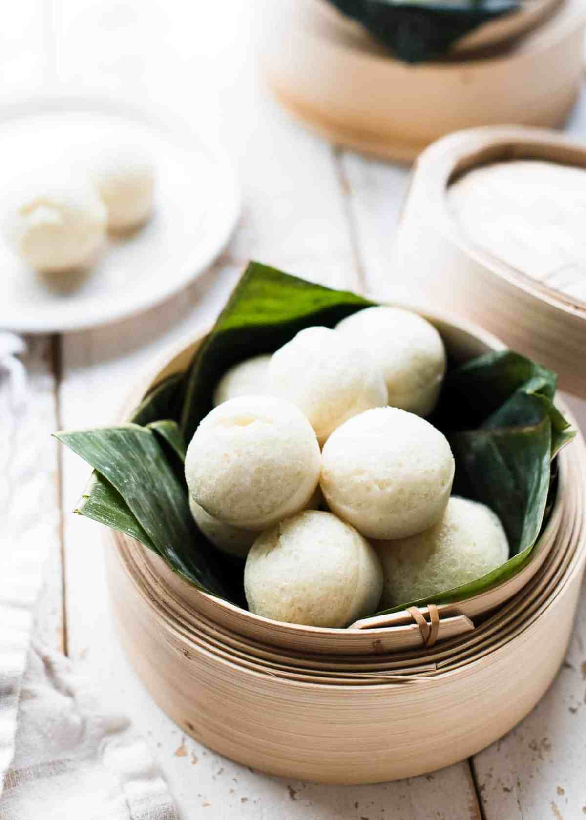 Bamboo steamer lined with banana leaves filled with steamed rice cakes, or puto.