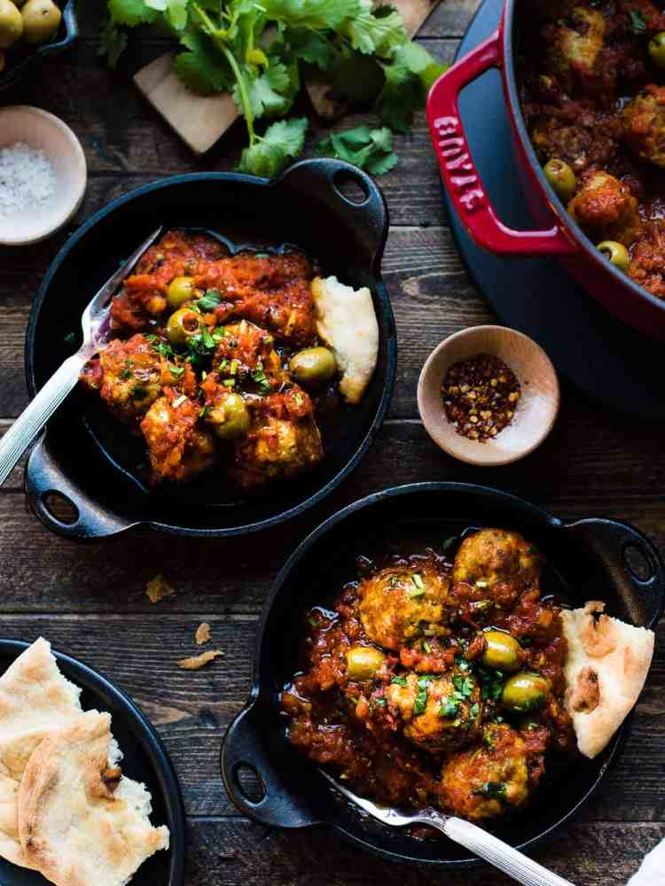 Albondigas with Olives in tomato sauce in black cast iron dishes.