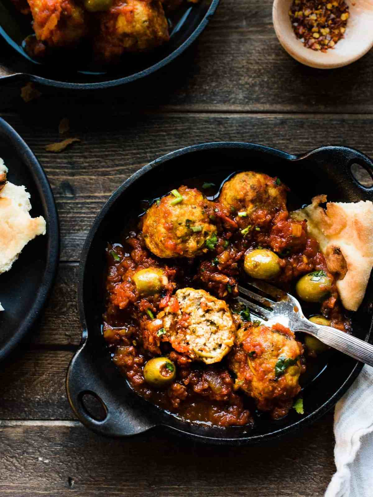Bowl of albondigas with olives in tomato sauce.