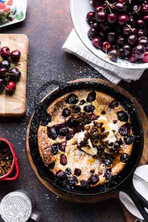 Cherry Dutch Baby Pancake with Pecan Streusel and cream in a cast iron skillet.
