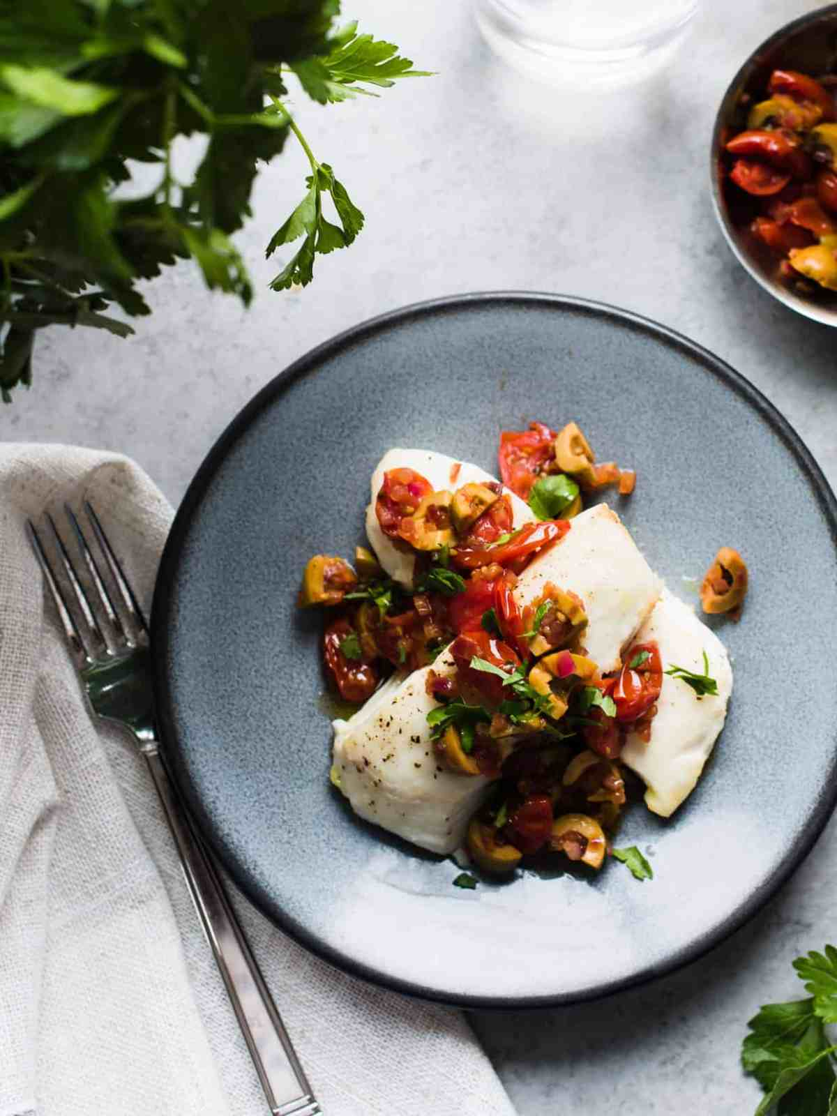 Baked halibut topped with a sauce of olives, onions, tomato and parsley.