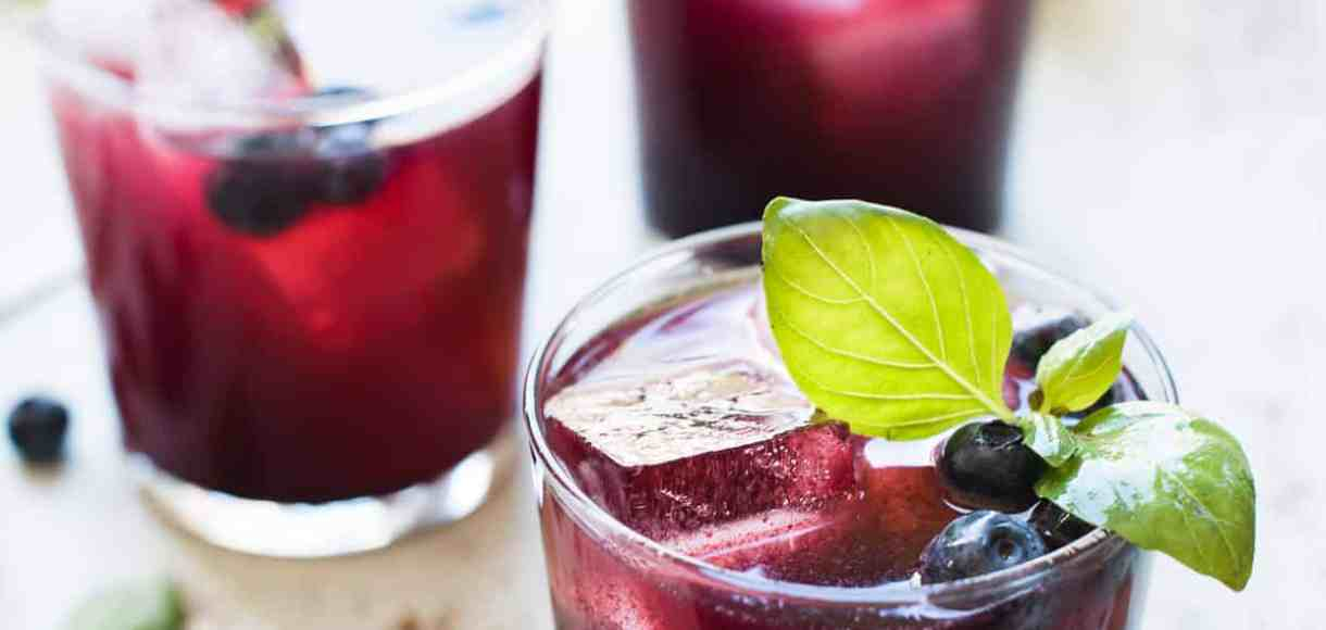 Glasses of blueberry ginger basil soda garnished with basil and blueberries.