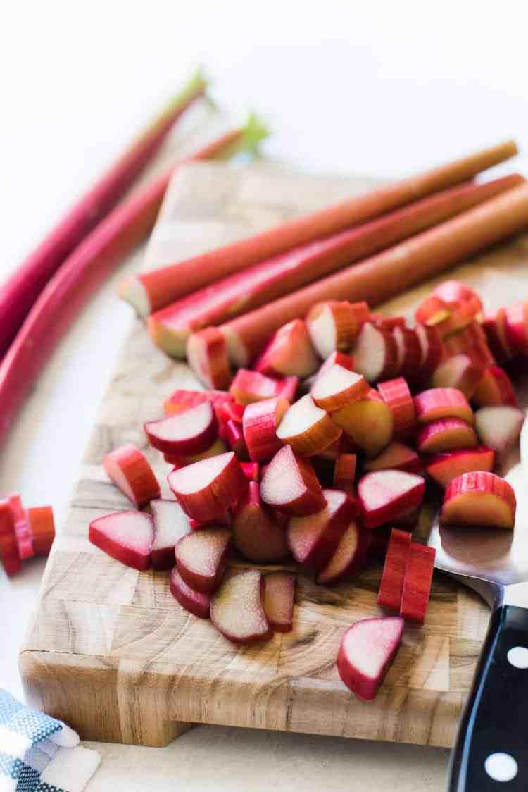 Slices of rhubarb on a cutting board for Rhubarb Frangipane Cake.