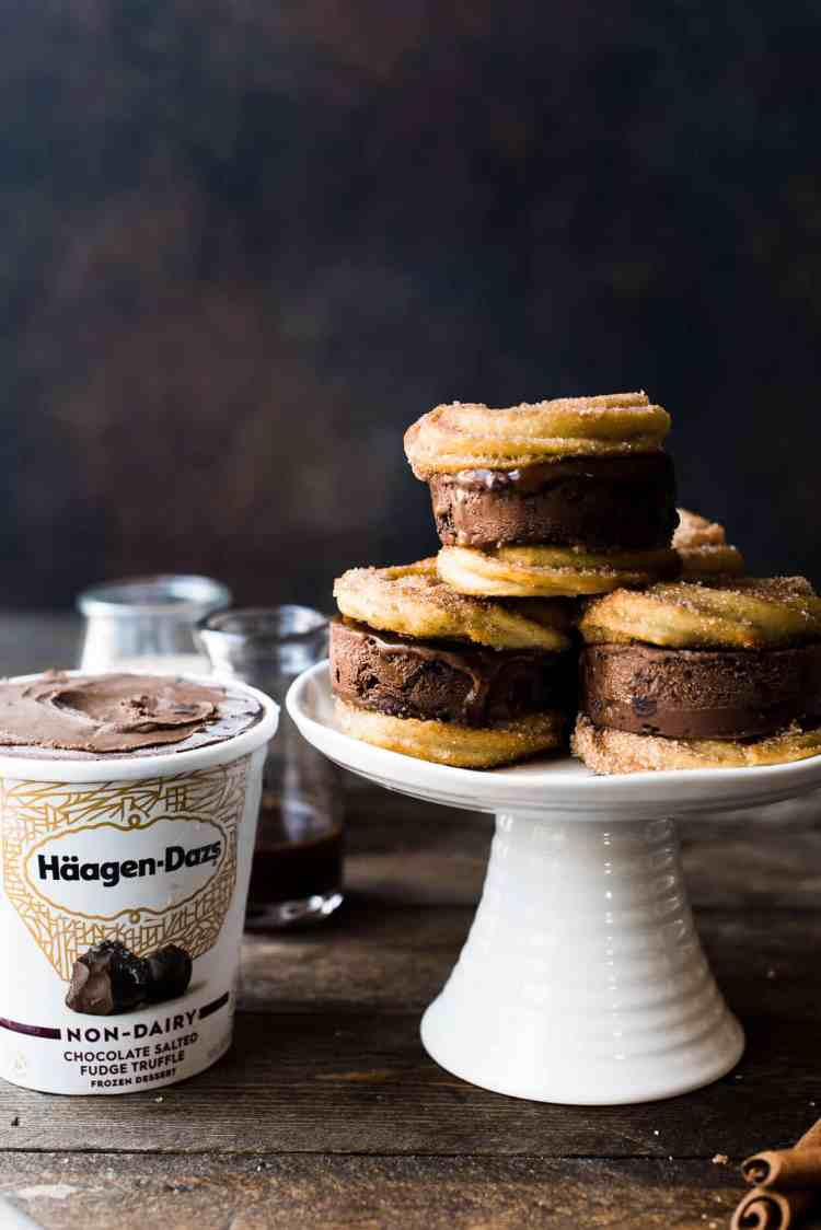 Baked Churro Baked Churro Ice Cream Sandwiches made with Häagen-dazs non-dairy Chocolate Salted Fudge Truffle Ice Cream on a white cake stand.