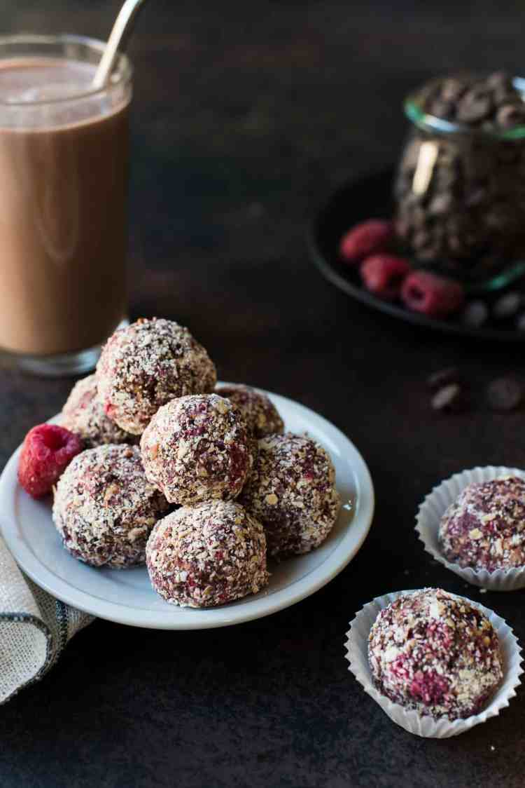Raspberry Peanut Butter Energy Bites with a glass of chocolate milk in the background.
