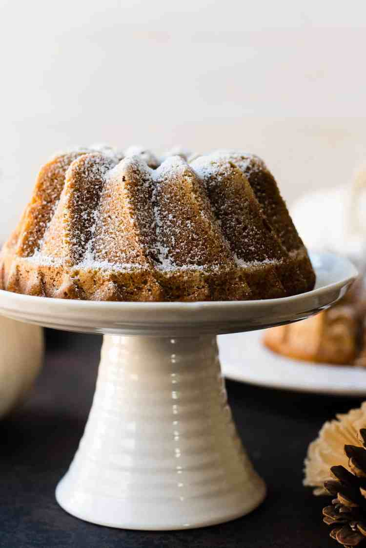 Close up shot of Pumpkin Spice Bundt Cake on a white cake stand.