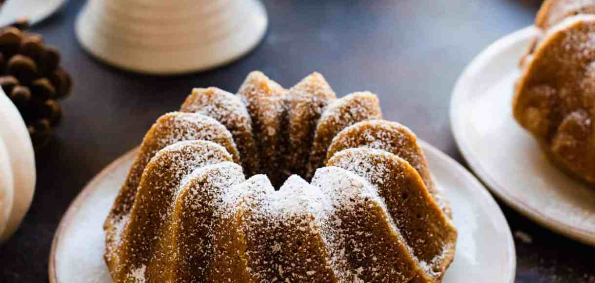Pumpkin Spice Bundt Cakes sprinkled with powdered sugar. White pumpkins and pine cones in background.