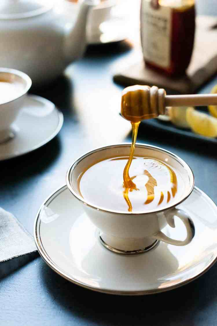 Drizzling honey into Homemade Fresh Ginger tea.