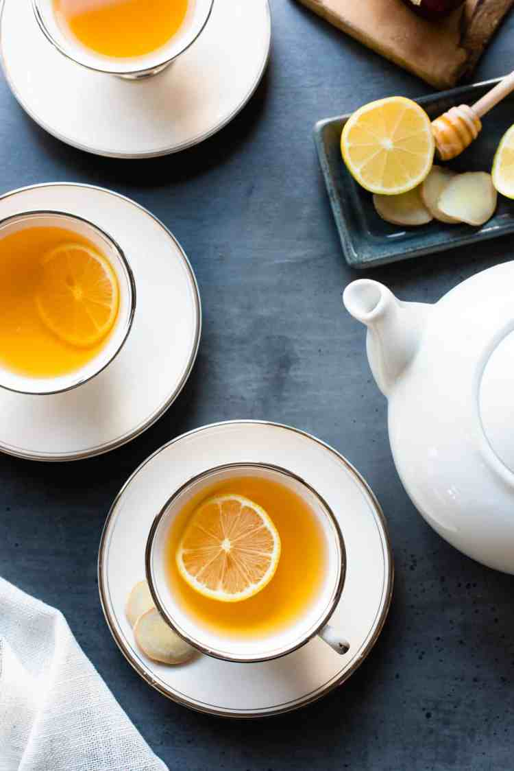 Cups of Homemade Fresh Ginger Tea with slices of lemon.