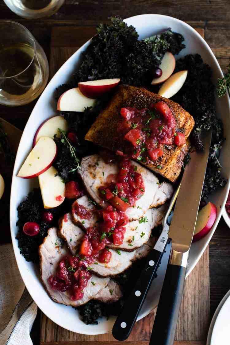 Roast Pork Loin with Apple Chutney, sliced, on a platter on a wooden table.