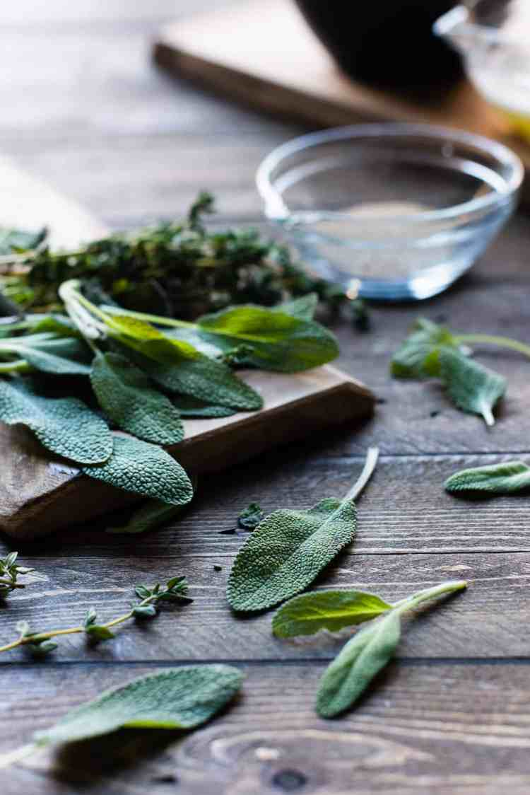 Fresh sage and thyme on a wooden table.