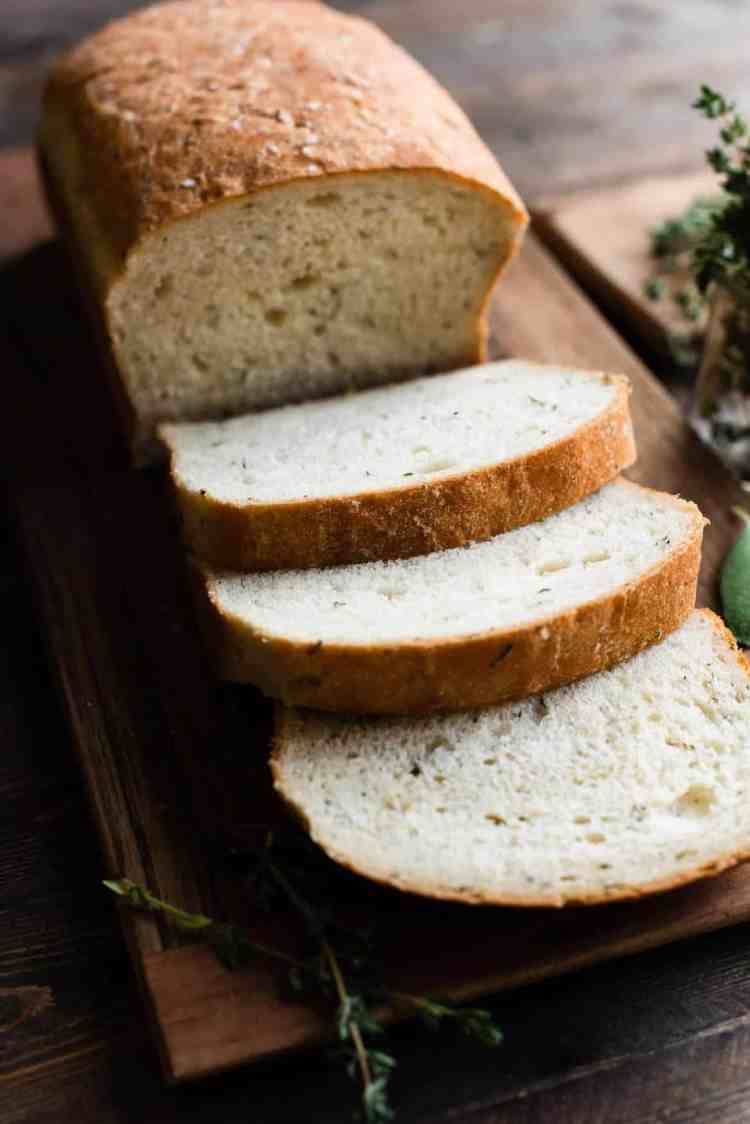 Savory Herb Stuffing Bread sliced on a wooden cutting board with herbs.