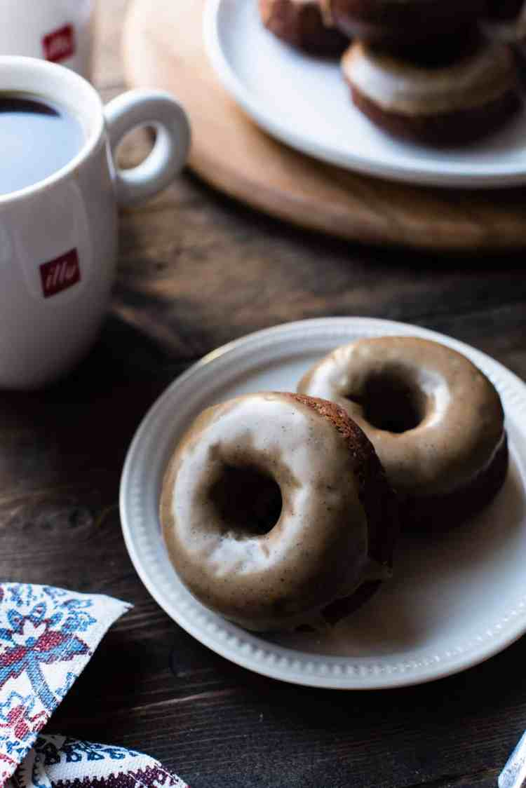 Two Coffee-Glazed Baked Chocolate Doughnuts on a dish with illy coffee.