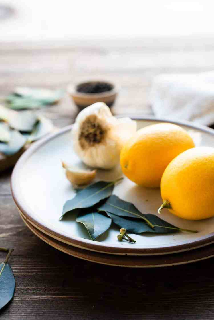 Bay leaves, garlic and lemon on a plate for Instant Pot Chicken Adobo.