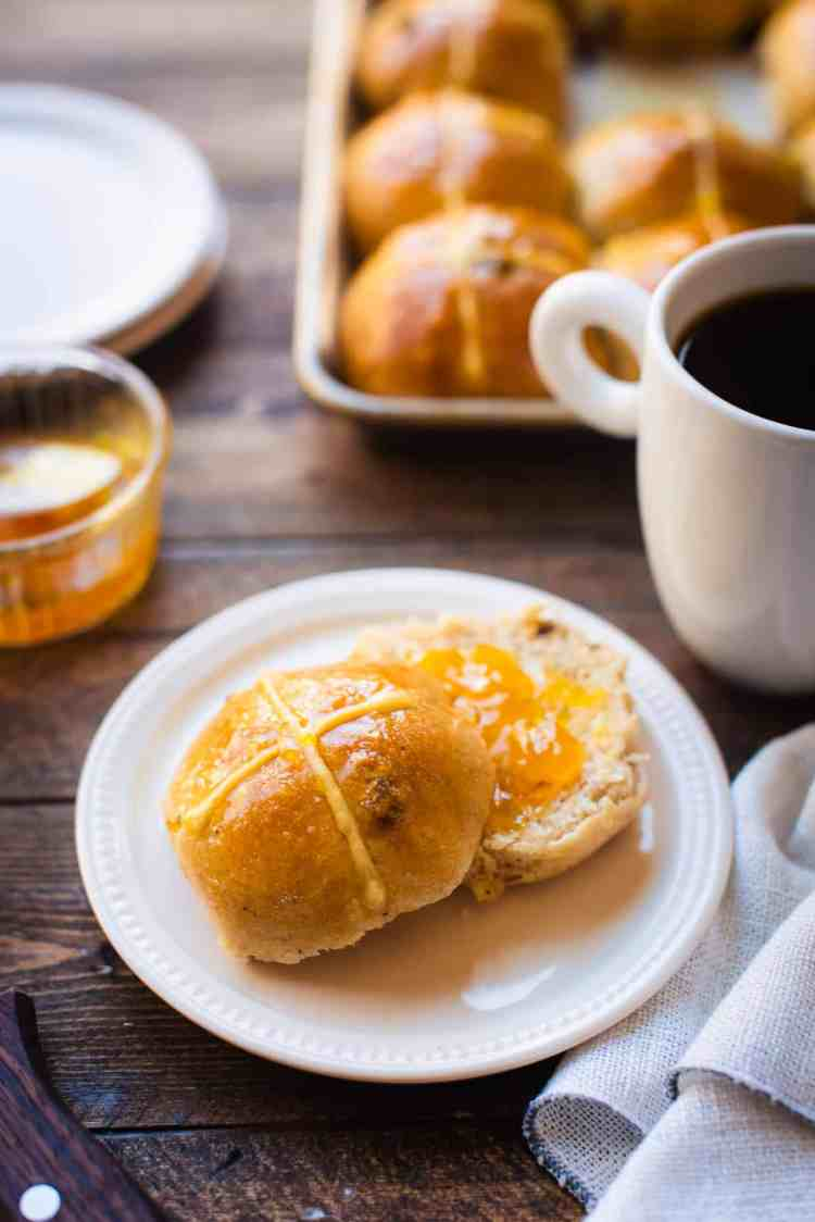 Hot cross bun with jam on a plate and served with coffee.