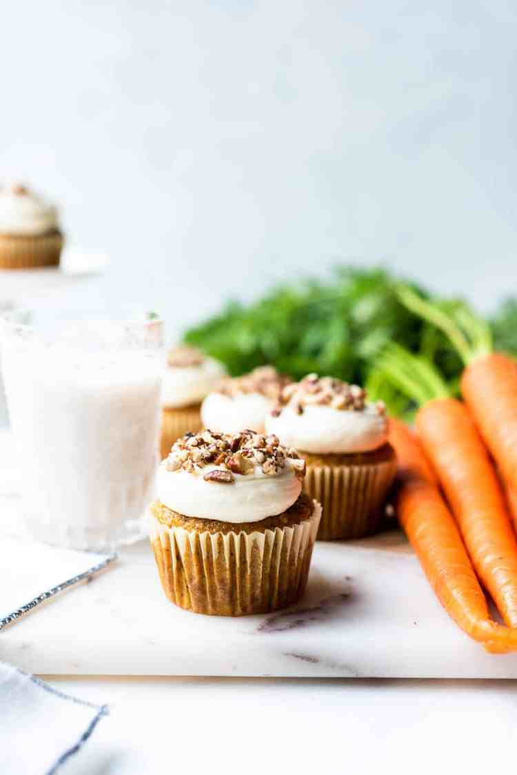 Vegan carrot cake muffins with cream cheese frosting topped with pecans and served with a glass of almond milk.