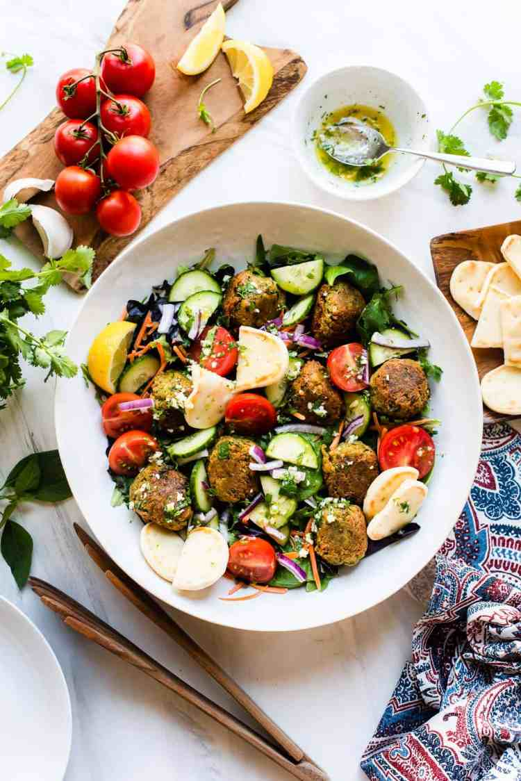 Falafel Salad made with canned chickpeas and served with Lemon Garlic Dressing in a serving bowl with dressing on the side.