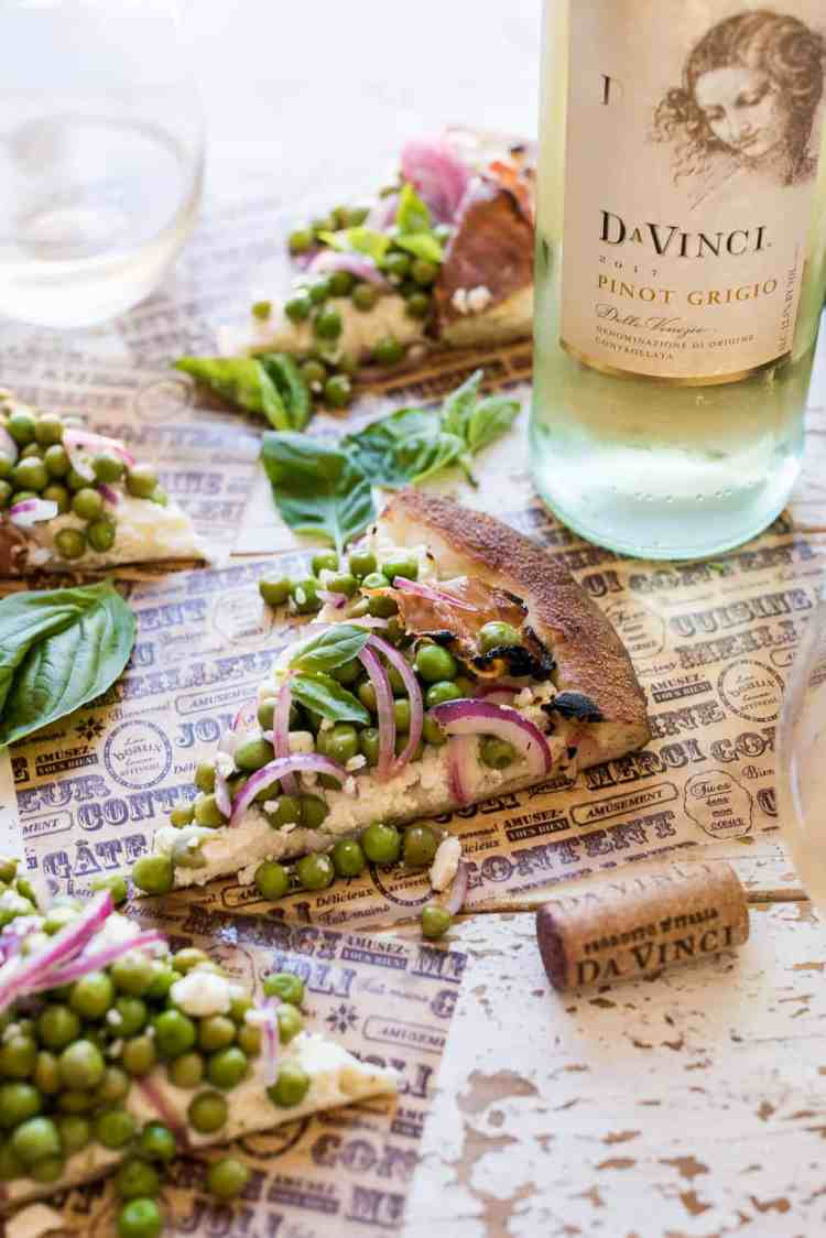A slice of Ricotta Pizza with Prosciutto and Fresh Pea Salad with Pinot Grigio