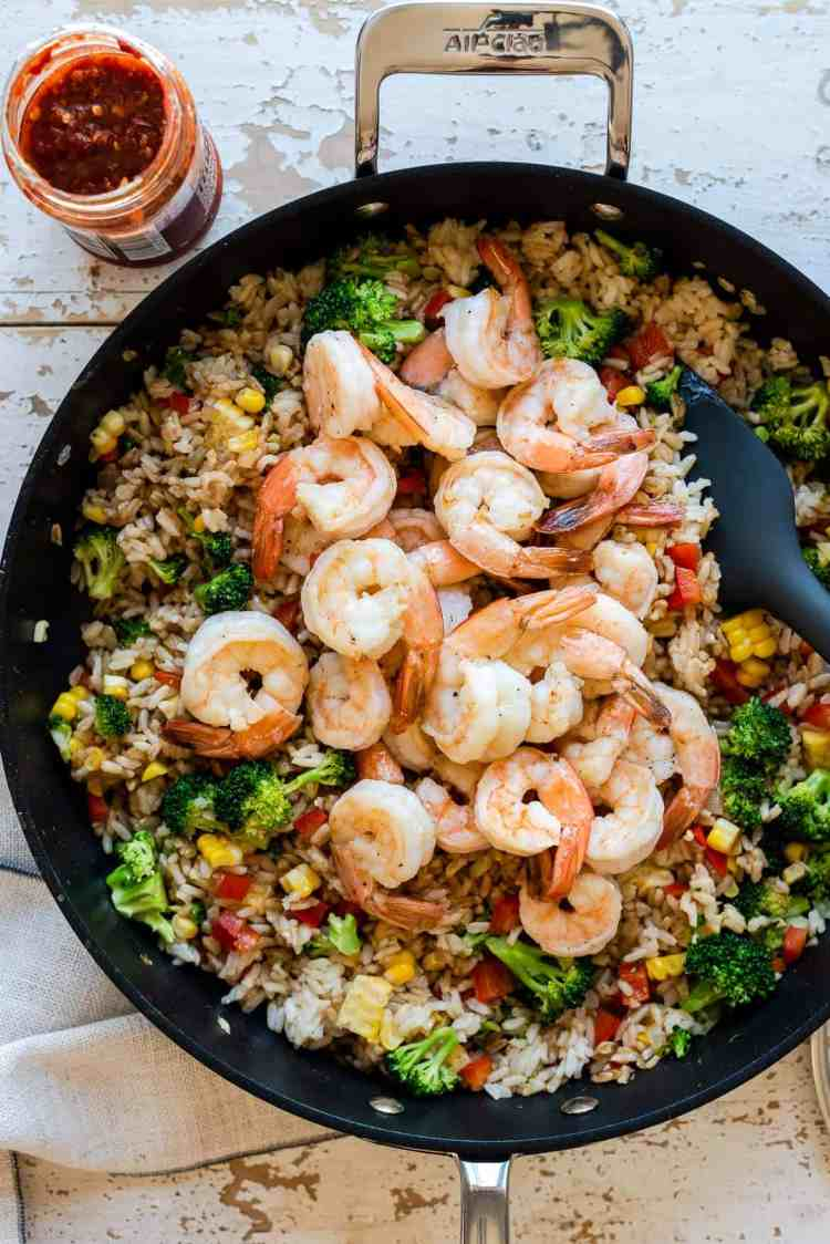 Adding shrimp to spicy fried rice in a nonstick skillet.